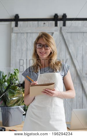 Young woman florist holds notebook