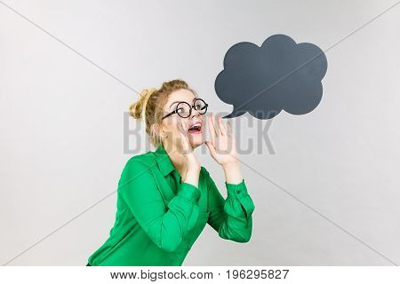 Business woman wearing green shirt and eyeglasses yelling telling something someone black thinking or speech bubble next to her.