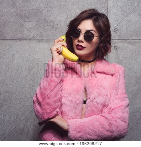 Young girl in pink fur and sunglasses using banana as phone posing on concrete wall.