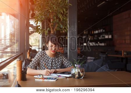 Young stylish woman sitting at table in cafe drawing in notebook.