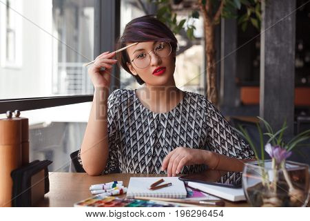 Young charming model in glasses sitting at table with paint and notebook looking at camera.