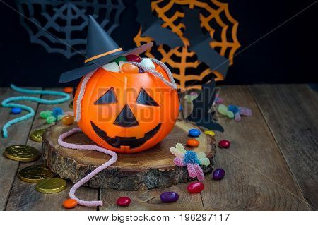 Halloween Jack o Lantern bucket overflowing with candy spooky Halloween decorations on background horizontal copy space