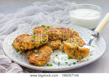 Vegetarian quinoa carrot coriander and green onion fritters served with yogurt on a plate horizontal copy space