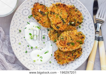 Vegetarian quinoa carrot coriander and green onion fritters served with yogurt on the plate horizontal top view