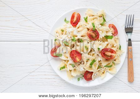 Pasta salad with tie pasta feta cheese cherry tomatoes mustard and basil top view copy space horizontal