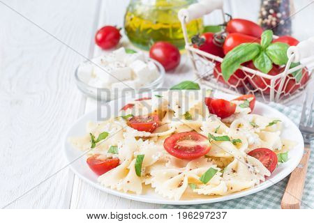 Pasta salad with tie pasta feta cheese cherry tomatoes mustard and basil copy space horizontal