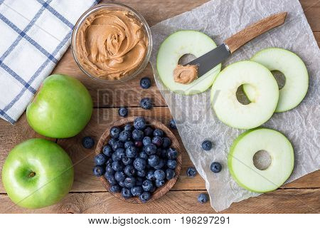 Healthy sandwich. Green apple rounds with peanut butter and and blueberries on wooden table horizontal top view