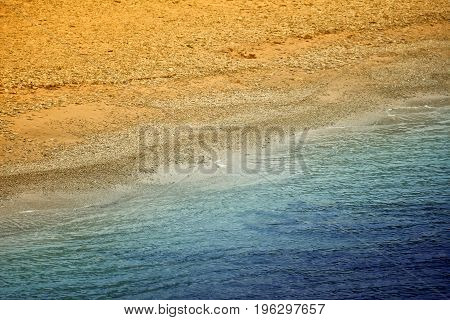 Edge of blue sea and yellow sand beach. Diagonal view