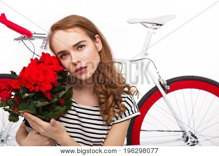 Lovely model in striped t-shirt holding flowerpot and posing on background of bicycle.