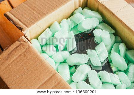 parcel of online shop, phone in a cardboard box on a green styrofoam.