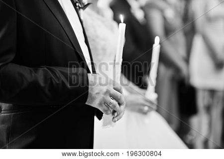 Newly Married Couple Holding Candles In The Church On Their Wedding Ceremony. Black And White Photo.
