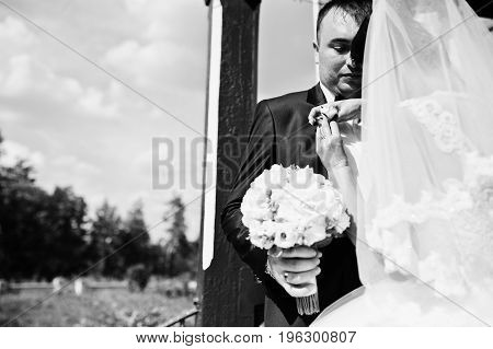 Gorgeous Young Bride Pinning Buttonhole Flower On Groom's Jacket Outdoor On Their Wedding Day. Black