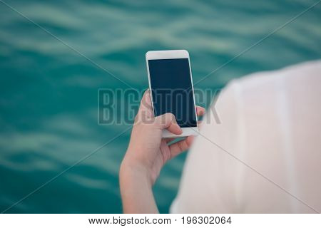 Rear view of female using blank screen mobile phone. Water surface in the background
