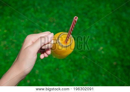Female hand holding glass bottle of fresh orange juice with drinking straw against green grass background. Healthy lifestyle concept.