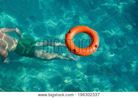 Lifebuoy and lifeguard in action under water