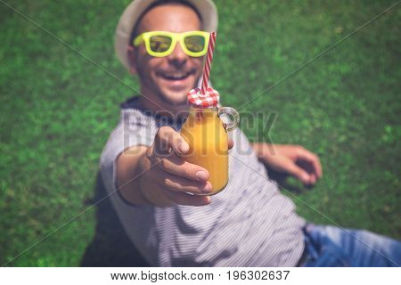 Portrait of young guy lying on the field and showing a glass bottle of fresh orange juice. Summertime and healthy lifestyle concepts.