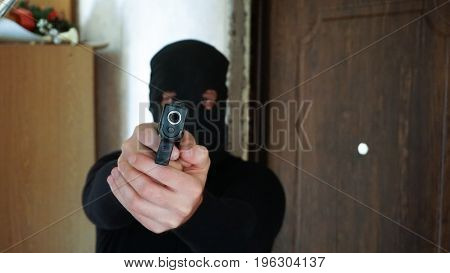Burglar Wearing Mask Aiming Gun Towards Camera.