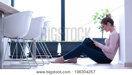 beautiful young women using tablet computer on the floor of her luxury home