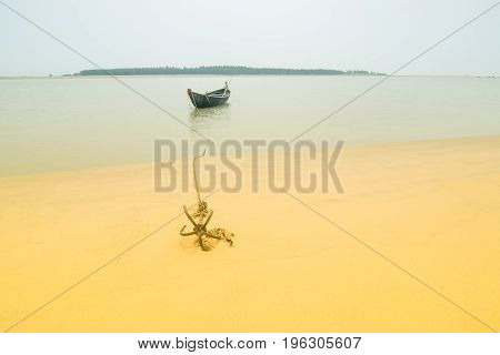 High key image of a boat on water tied by a rope with an anchor on river bed. Tajpur West Bengal India. Minimalistic image.