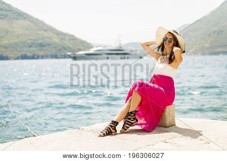 Young Attractive Woman With A Hat And Glasses Poses By The Sea