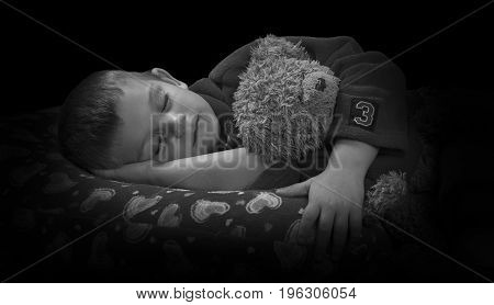 Funny boy with a teddy bear on pillow before falling asleep artistic conversion
