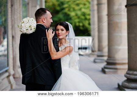 Fabulous Wedding Couple Walking And Posing Next To The Columns On A Bright Wedding Day.