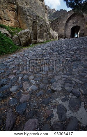 Entrance to the ancient Geghard monastery paved by cobblestones Armenia