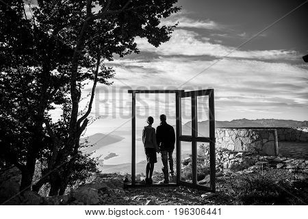A loving couple hold hands and look forward to the future black and white