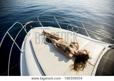 Young Attractive Woman Lies And Sunbathing On The Bow Of A Luxury Yacht