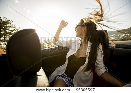 Young Attractive Woman Poses In Cabriolet At Seaside