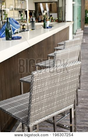 Beautiful elegant interior design bar counter top with rattan chairs