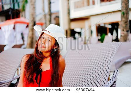 Beautiful young woman sitting on sunbed with the hat on the beach resort summer vacation