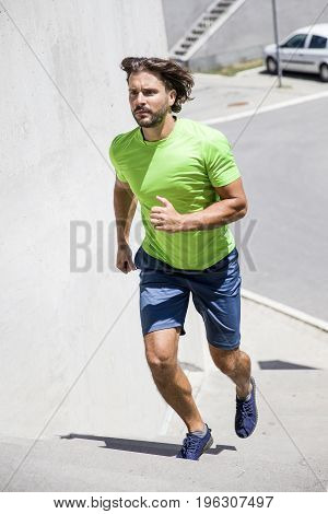 Young man running on the street in urban environment at sunny day