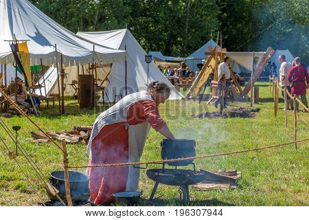 Useldange, Luxembourg - July 06, 2017: Medieval Woman in medieval clothes preparing lunch on historical in Medieval Fair festival.