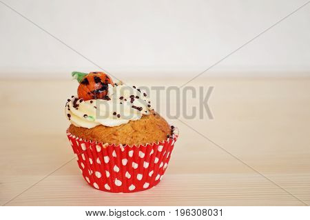 Cupcake decorated with cream and marzipan pumpkin on Halloween on the beige background