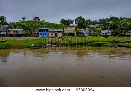 Remote village with typical wooden shack housing on the banks of the Amazon in Peruvian rainforest