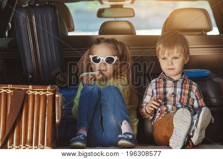 Travel by car family together brother and sister sitting in a trunk