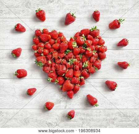 Heart symbol from strawberry on white wooden background. Fruits diet concept. Top view. High resolution product