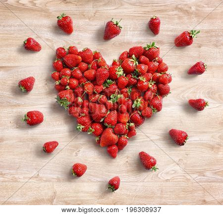 Heart symbol from strawberry on wooden background. Fruits diet concept. Top view. High resolution product