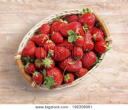 Organic strawberry in basket on wooden background. Fruits diet concept. Close up top view high resolution product