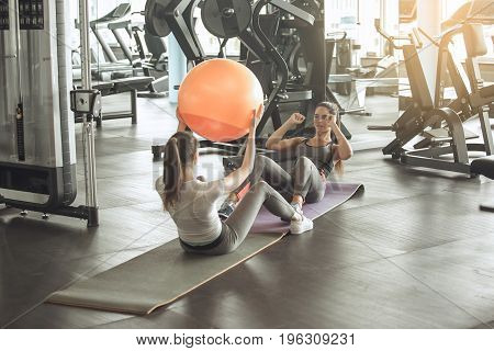 Young female friends exercise in the gym personal trainer