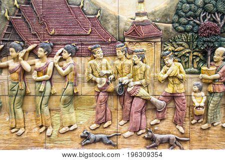 Thai lifestyle stone carving on the wall (H?e Glong Yaao or Thai long drum parade ) at at Wat Tai Phra Chao Yai Ong TueUbonratchathani ProvinceThailand.