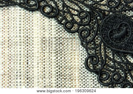 Detail of black lace on rough simple fabric closeup background
