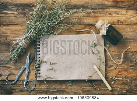 bunch of herb wormwood jars of oil scissors notebook and pencil on an old wooden table rustic style vintage