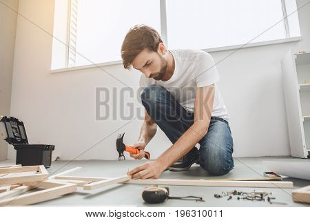 Young male does apartment repairment himself construction