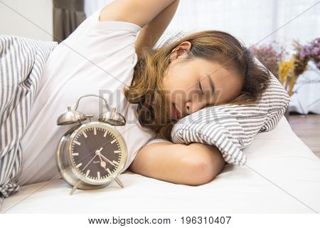 Young asian woman lying in bed watching the clock, Young woman don't want to wake up, Young woman is so broken hearted to get out of bed