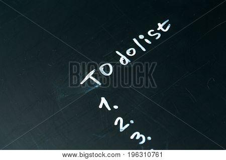 inscription do it list drawn with chalk on a school blackboard dark.