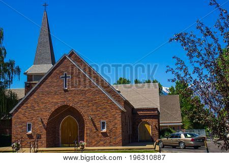Brick Church With Steeple Against Blue Sky Background