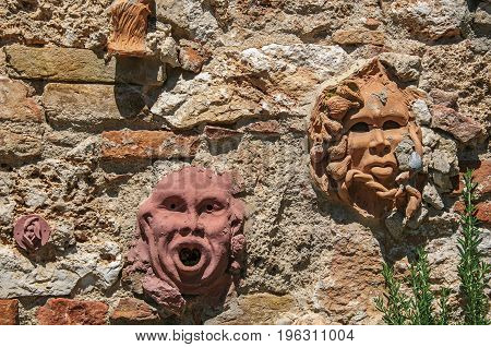 Close-up of clay masks attached to the wall in Colle di Val d'Elsa. A graceful village with its historic center preserved and known by its crystal production. Located in the Tuscany region