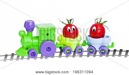 Ripe cherry tomatoes in a toy train. Funny characters from the original idea of the concept.